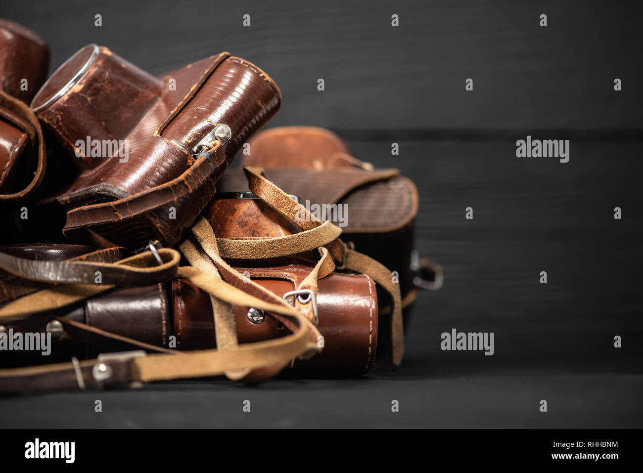 Heap of 35mm analog cameras in leather covers on black background Stock Photo