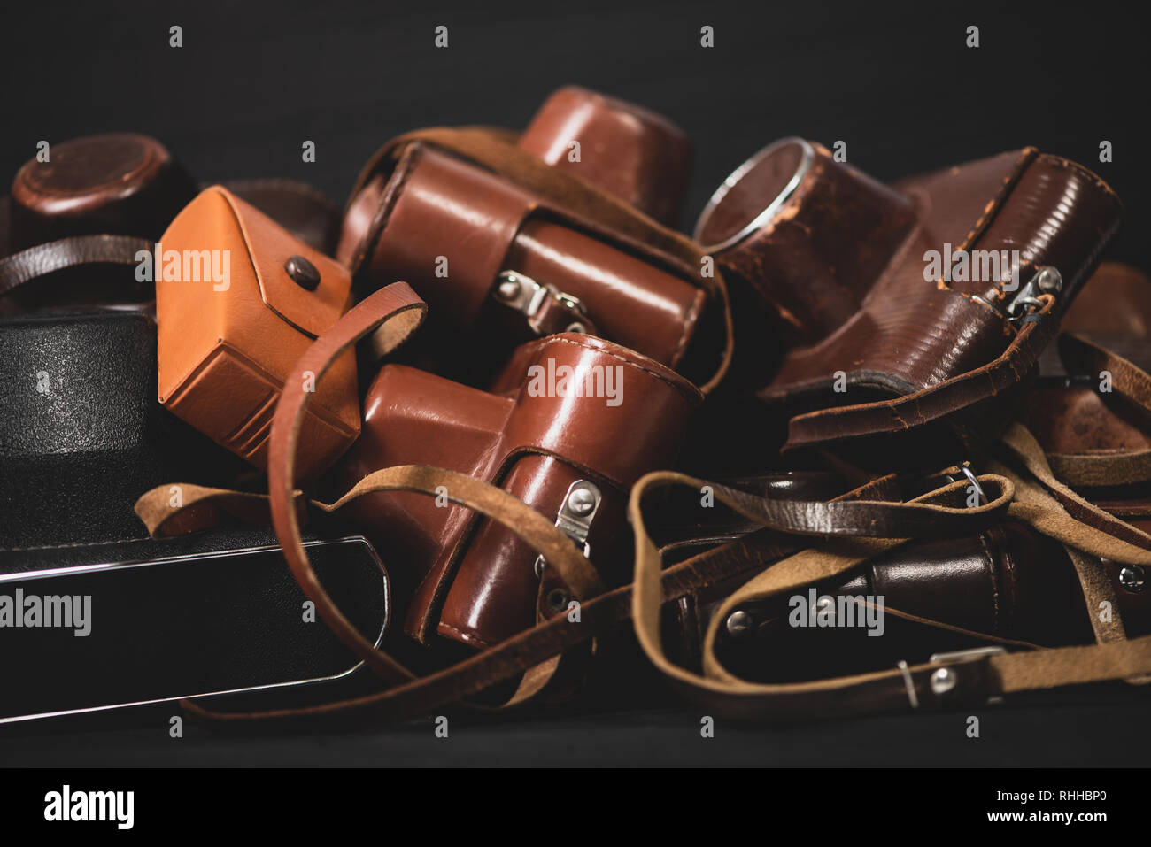 Heap of 35mm vintage cameras in leather covers. Collecting Stock Photo