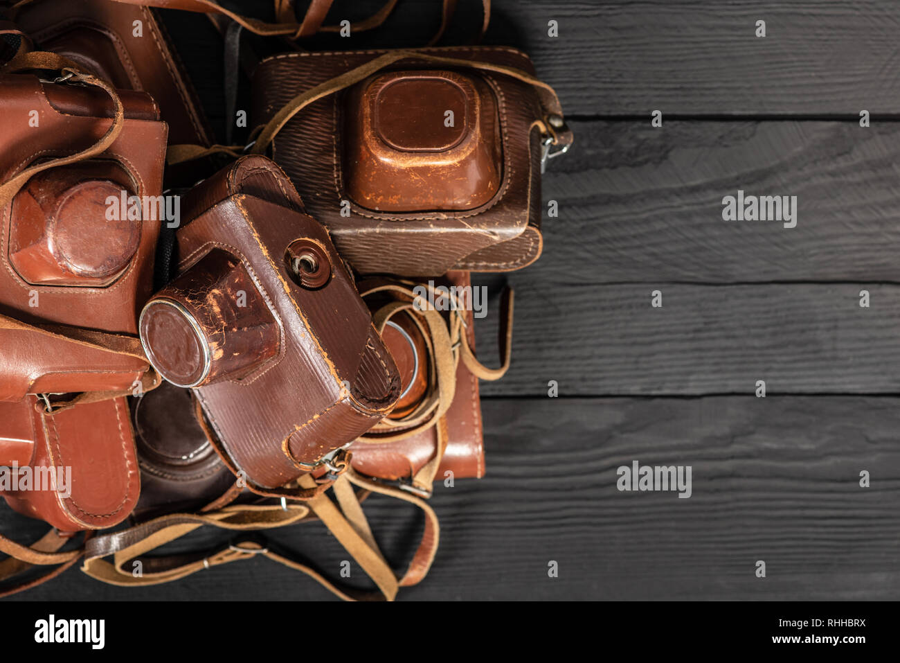 Heap of 35mm retro cameras in leather covers on black, top view. Collection of old things and antiques, auctions Stock Photo
