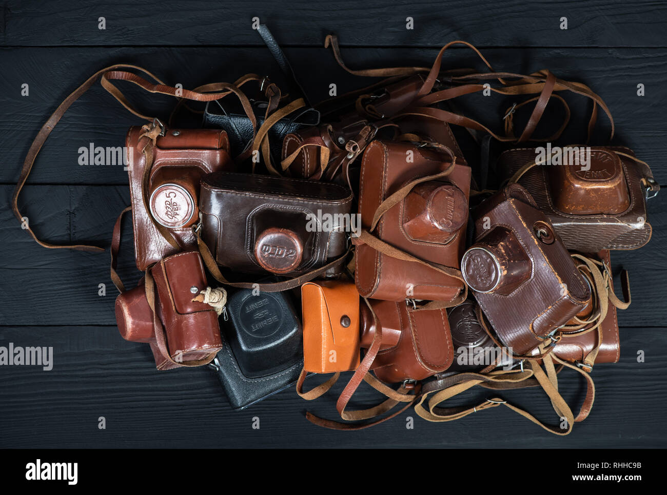 Drohobych, Ukraine - 02 February, 2019: Heap of 35mm retro cameras in leather covers on black, top view Stock Photo
