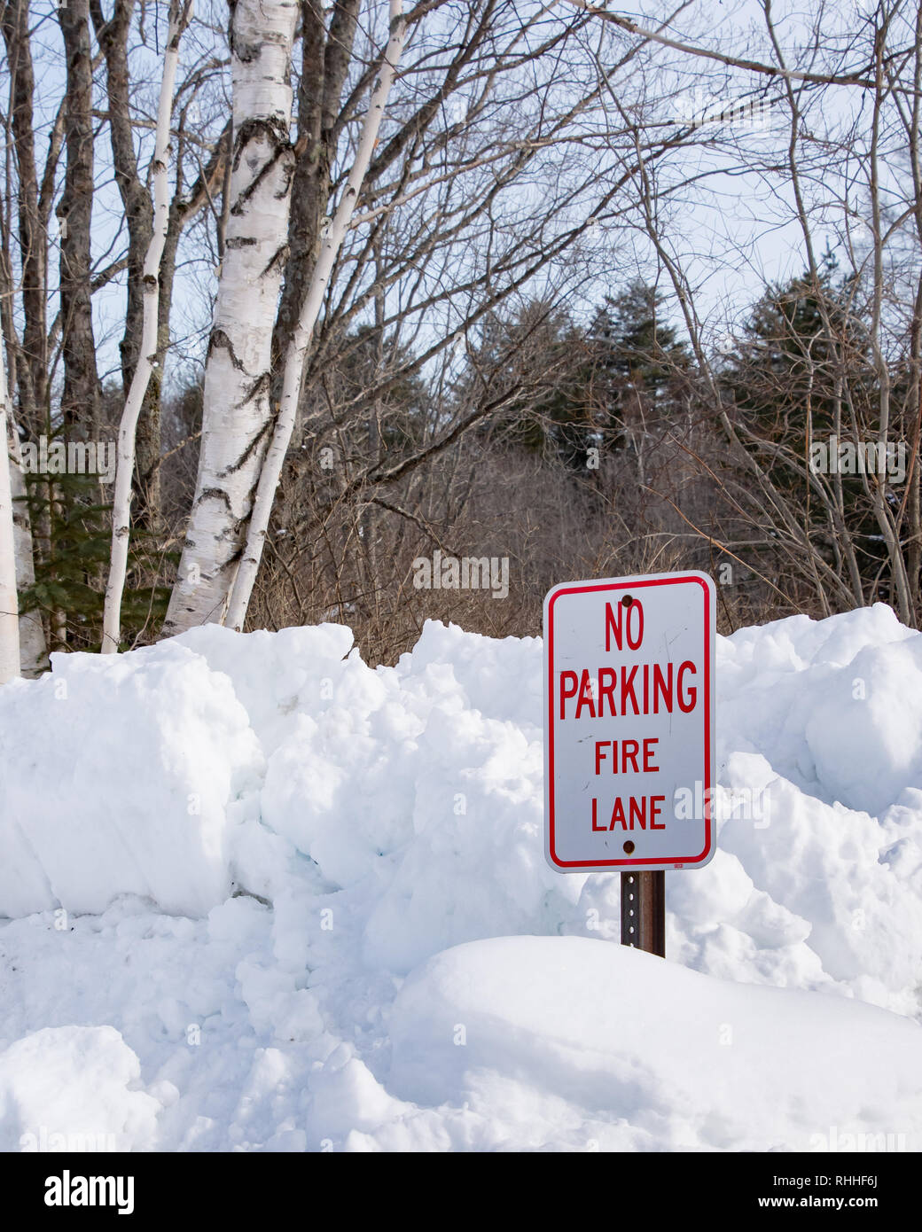 """No Parking Fire Lane"" sign on snow bank near the Sacandaga River in Speculator, NY keeping the area open for fire trucks to draw water from the river Stock Photo"