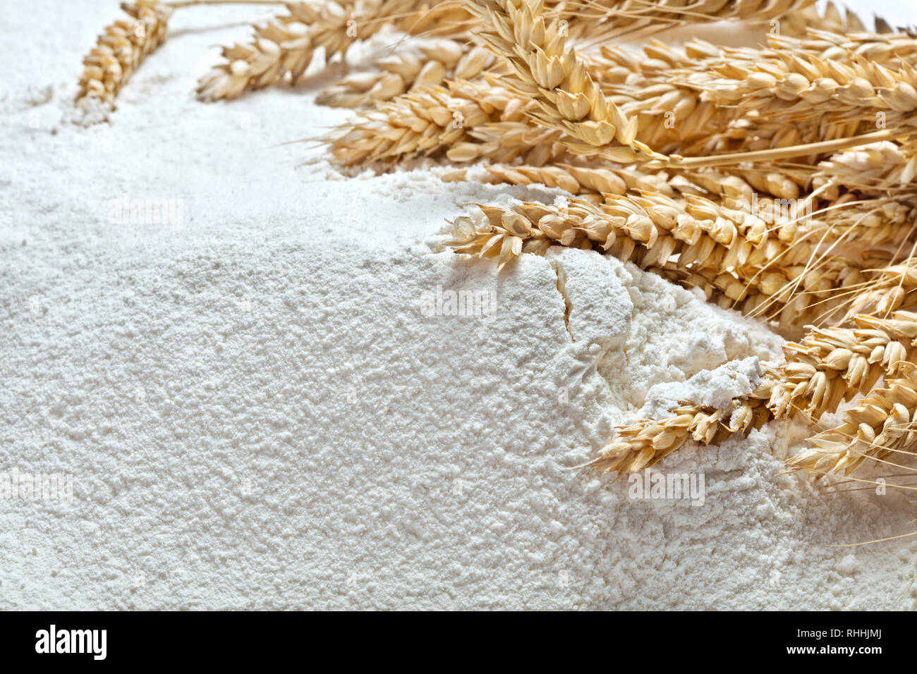 heap of wheat flour with ears of wheat - Stock Image