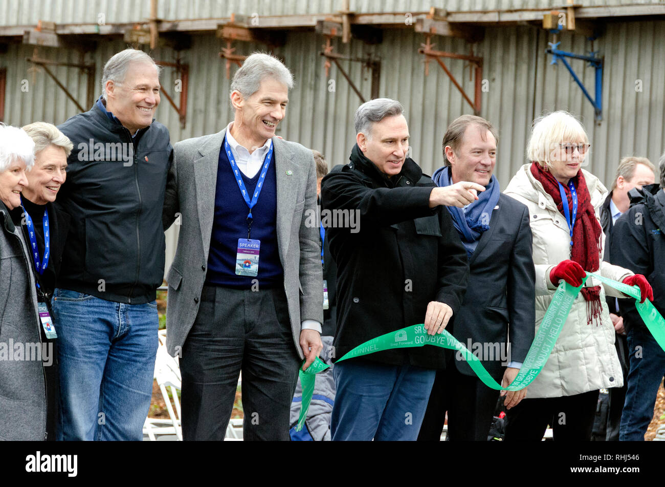 Washington, USA. 2nd Feb 2019. Washington State Governor, Jay Inslee (left) leads the ribbon cutting ceremony to formally open the new SR99 tunnel in Seattle, Washington ouside the tunnel upper deck entrance. The 2-mile long tunnel which took seven years to complete after overcoming difficulties during the tunnel drive, will open to traffic following celebrations to honor it's ultimate success. Credit: Catherine Bassetti/Alamy Live News - Stock Image