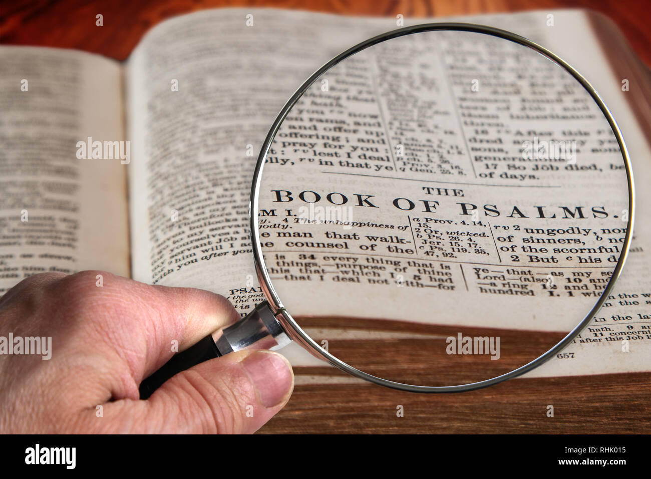 Hand holding magnifying glass over an old Bible opened to