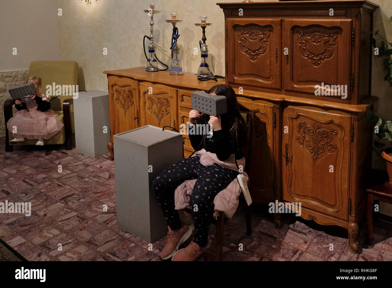 Young girls using virtual reality glasses inside an installation by media artist Daniel Landau which combines the home environments of a Jewish and Arab family part of an exhibition entitled Together or Alone displayed at the Youth Wing in Israel Museum in West Jerusalem Israel - Stock Image