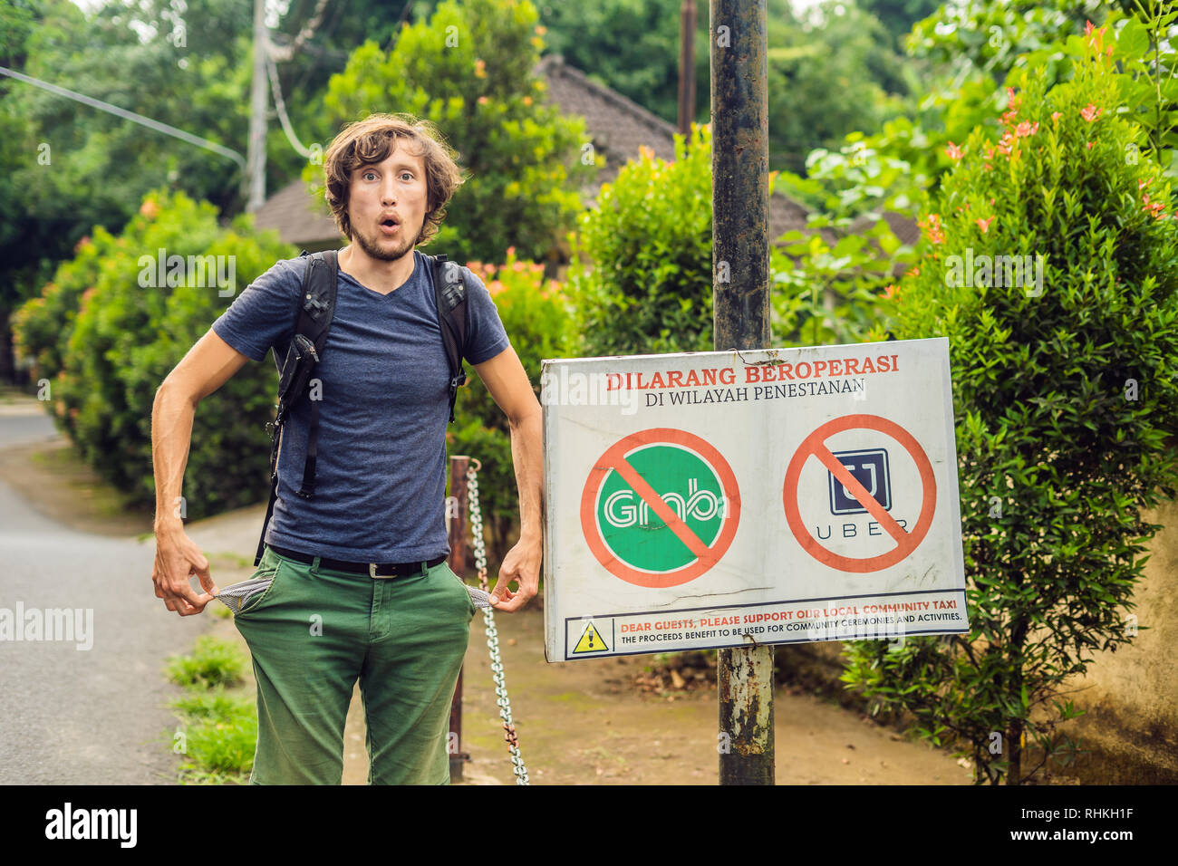 BALI, INDONESIA - 21 May, 2018: Young man looks at protest sign on a wall in Indonesian objecting to Uber and Grab taxi drivers reads 'Uber and Grab - Stock Image