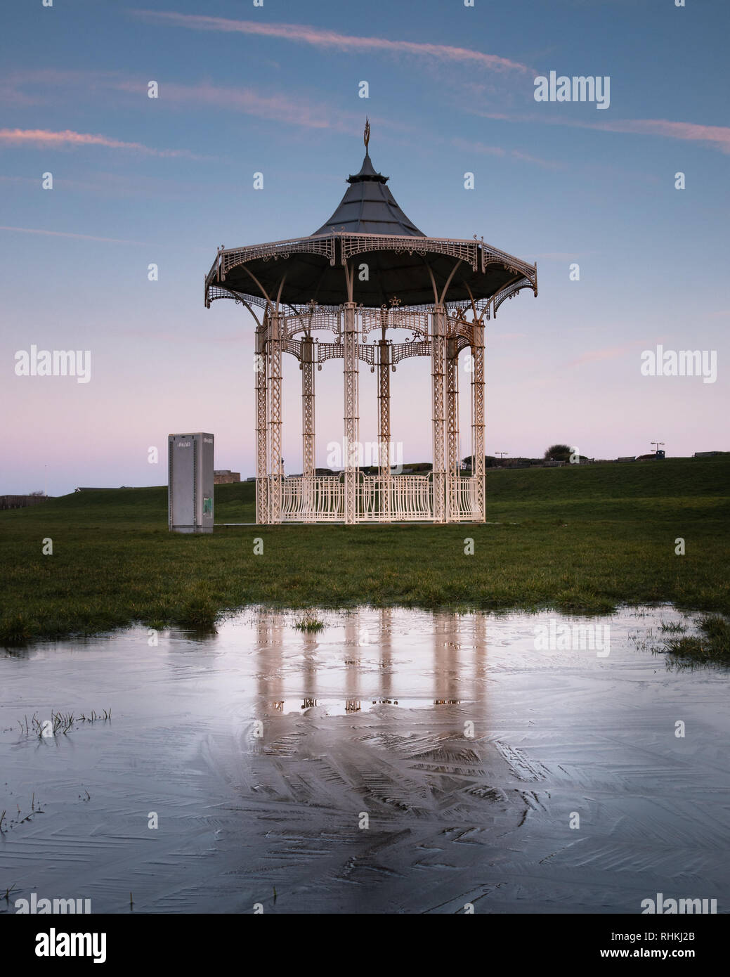 Reflections of Southsea Bandstand in frozen water at sunrise - Stock Image