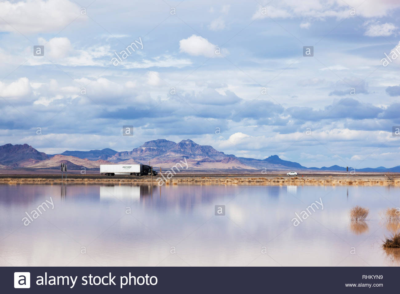 Traffic on Interstate 10 in southwestern New Mexico, USA, reflected in water standing in playa - Stock Image