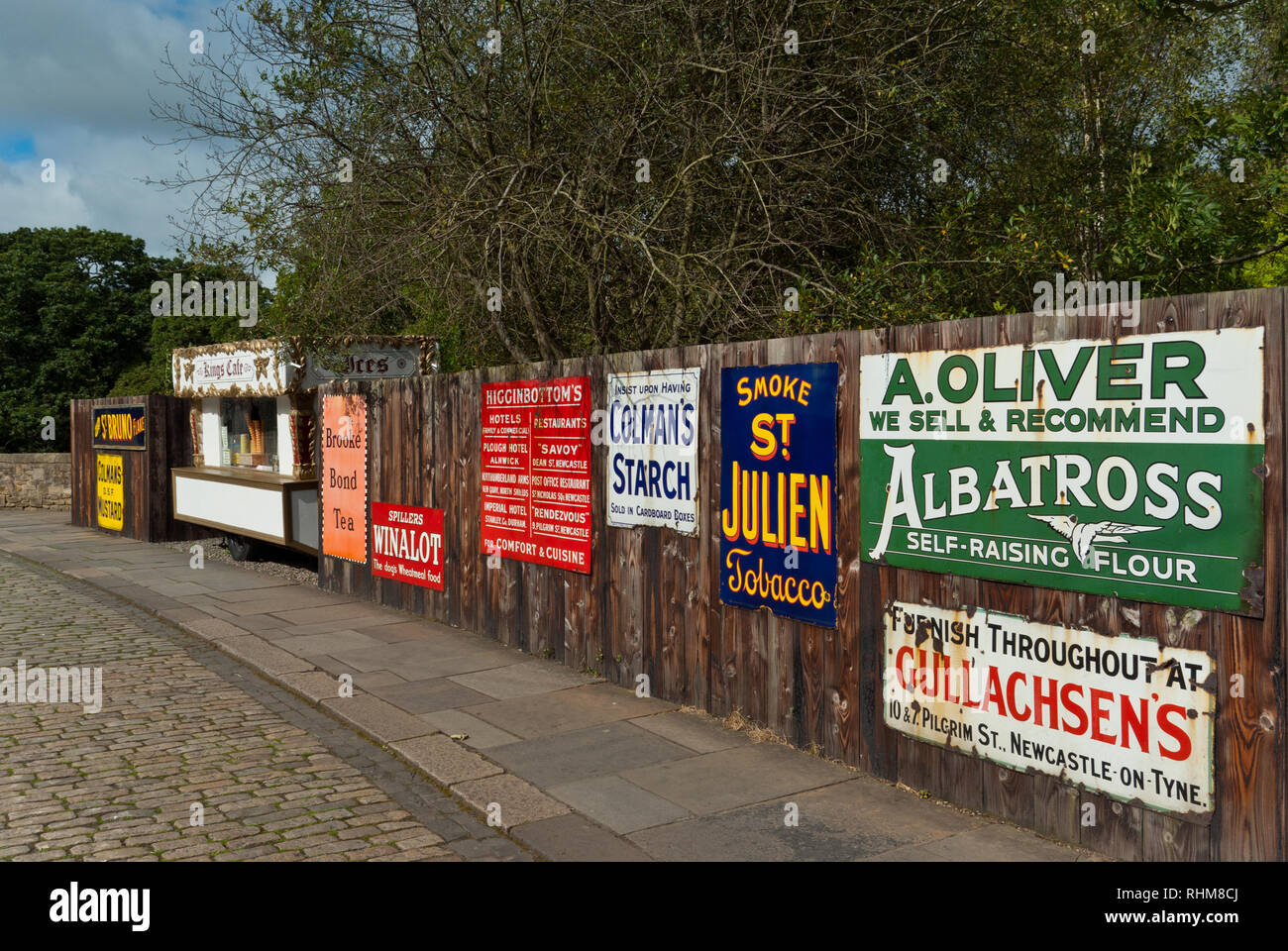 Fence displaying a selection of vintage metal advertising signs, Beamish Museum, Co Durham, England, UK - Stock Image