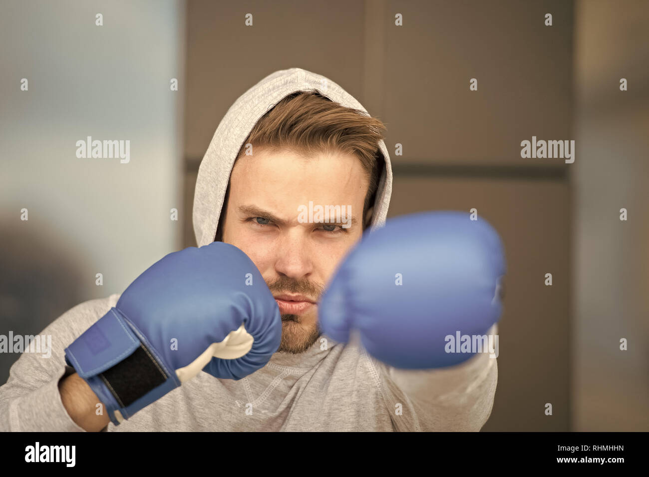 Boxing concept. Man athlete on concentrated face with sport gloves practicing boxing punch, urban background. Boxer with hood on head practices jab punch. Sportsman boxer training with boxing gloves. - Stock Image