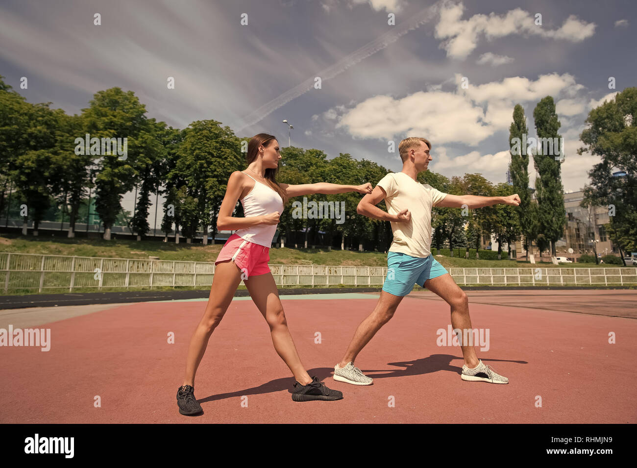 Couple workout and punching. Sport and fitness. Man and woman sunny outdoor on blue sky. Summer activity and energy. Coach and health. - Stock Image