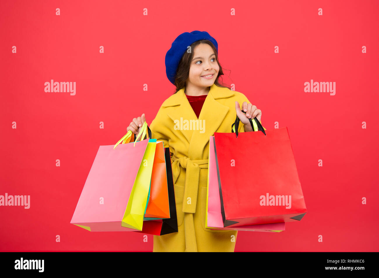 Obsessed with shopping. Girl cute kid hold shopping bags. Get discount shopping on birthday holiday. Nice purchase. Fashionista enjoy shopping. Customer satisfaction. Prime time buy spring clothing. - Stock Image