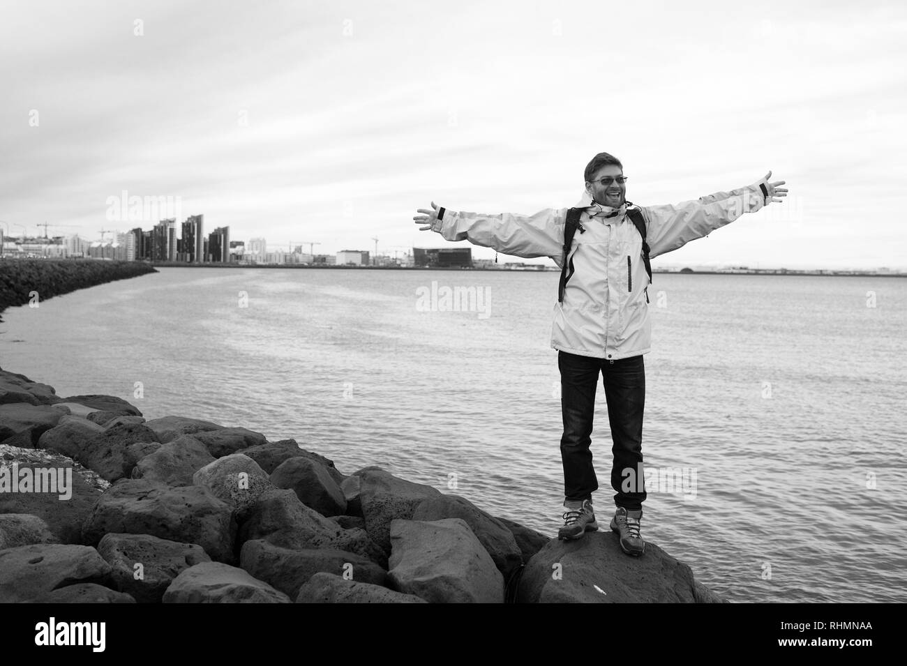 Man tourist wear warm protective clothes for cold climate conditions. Tourist well equipment ready explore scandinavian or nordic country. Tourist traveller concept. Tourist on sea background. - Stock Image