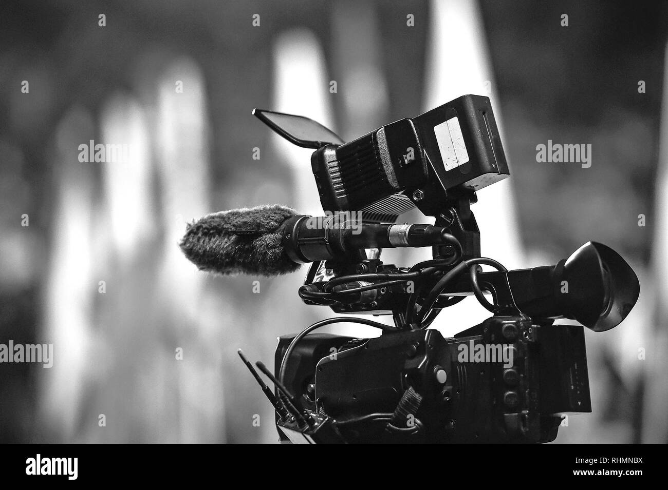 Modern digital television or video camera, camcorder, recorder in studio on blurred colorful background. Broadcasting, media, entertainment - Stock Image