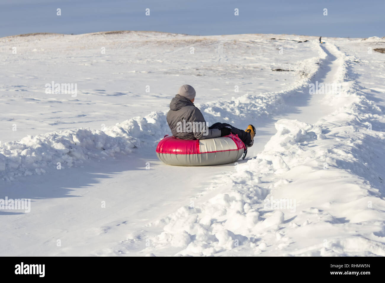 A young man riding a tubing down the hill from the hill, winter sport. - Stock Image