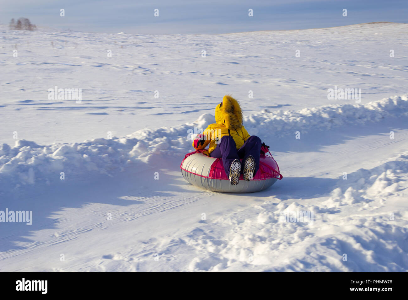 The girl rides a tubing down the snowy road, winter sport. - Stock Image