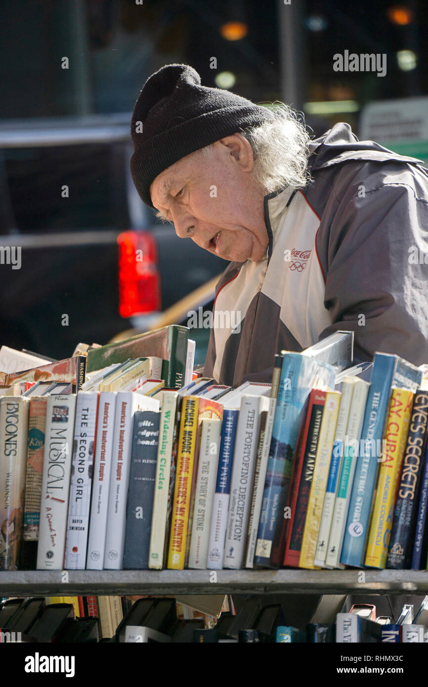 An older man shops for on sale books on the racks outside of the Strand Book Store on Broadway in Greenwich Village, New York City. - Stock Image