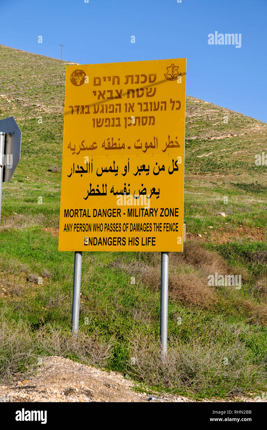 Israel, Golan Heights. The Syrian Israeli border fence a yellow warning sign as seen from the Israeli side - Stock Image