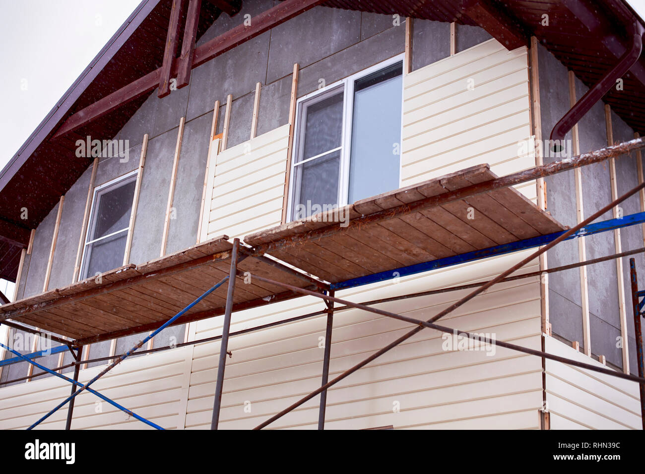 Scaffolding around house with beige siding covering walls. Construction site. - Stock Image