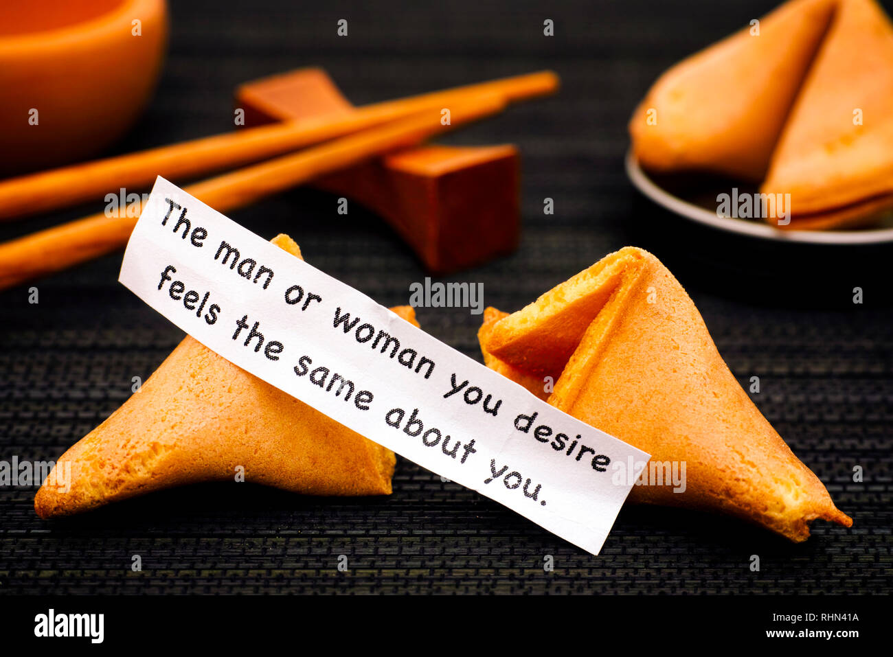 Paper strip with phrase The Man or Woman You Desire Feels the Same About You. from fortune cookie, another cookie and chopsticks on black napkin backg - Stock Image