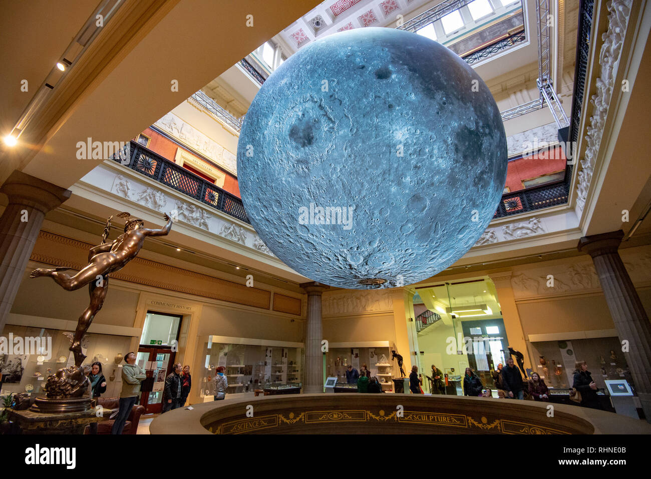 Preston, UK. 03rd Feb, 2019. The Flying Mercury statue seems to salute The Museum of the Moon, an artwork by Luke Jerram, at the Harris Museum and Art Gallery, Preston, Lancashire. The seven metres in diameter sphere will tour various exhibitions and festivals around the world. Credit: John Eveson/Alamy Live News - Stock Image