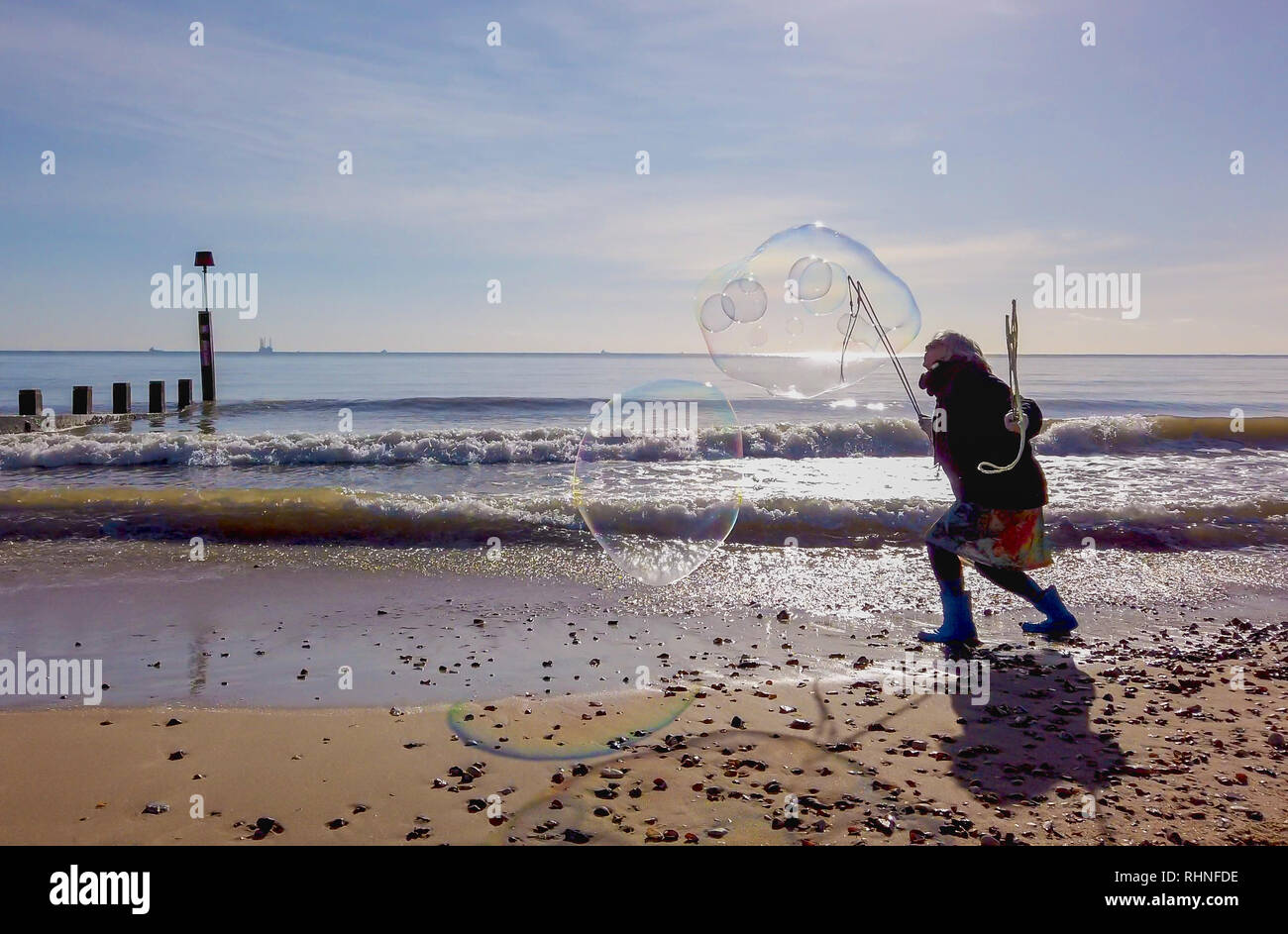 Bournemouth, UK. Sunday 3rd February 2019. A lady makes large bubbles on the beach in Bournemouth in Dorset, on a sunny winters day. Credit: Thomas Faull/Alamy Live News Stock Photo