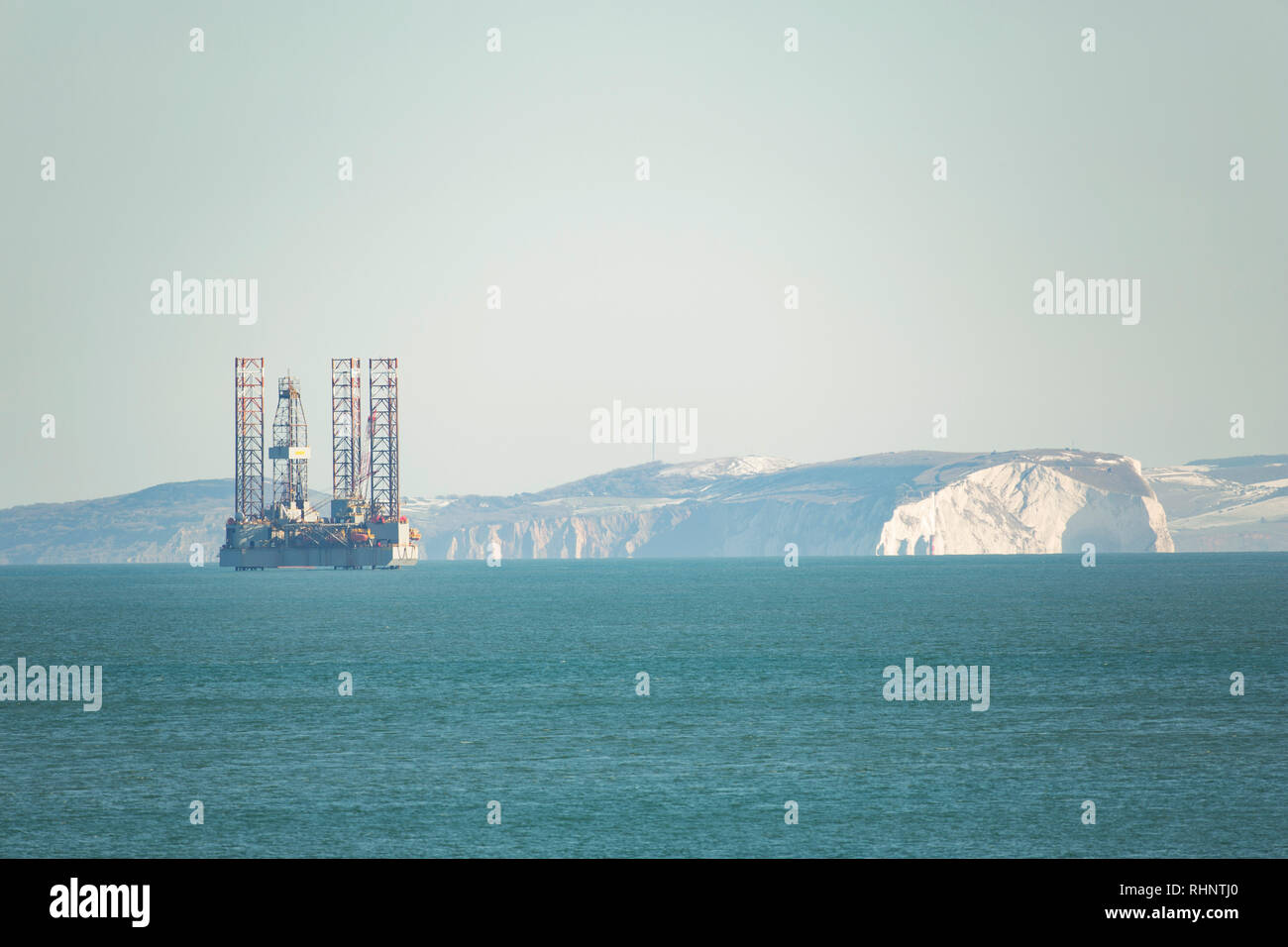 An ENSCO 72 oil rig against a backdrop of the Isle of Wight. The rig will be drilling to a depth of more than 1000 metres into the seabed in th Stock Photo