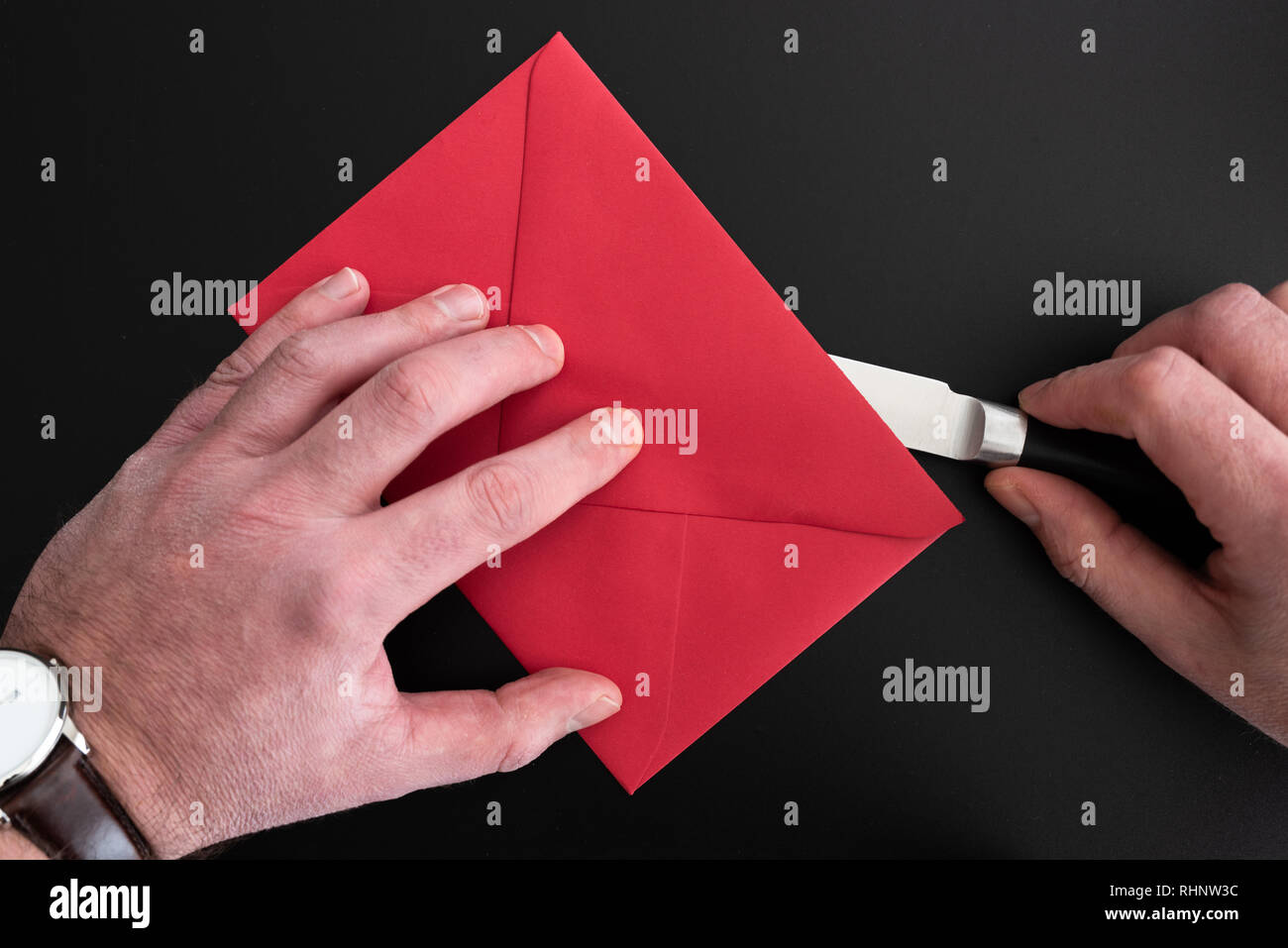 hands of man opening red envelope with paper knife - Stock Image