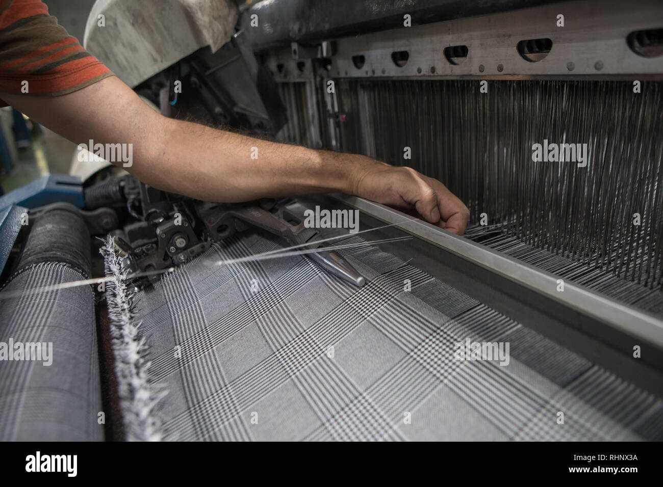 Hand on weaving loom machine. A loom machine for clothing or woven label. Weaving machine for garment industry. Weaving loom in textile factory. Stock Photo