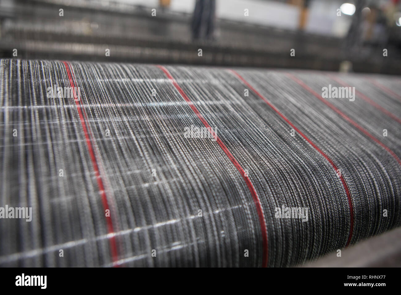 Yarn thread lines on the weaving loom machine. A loom machine for clothing or woven label in textile factory. Weaving machine for garment industry. - Stock Image