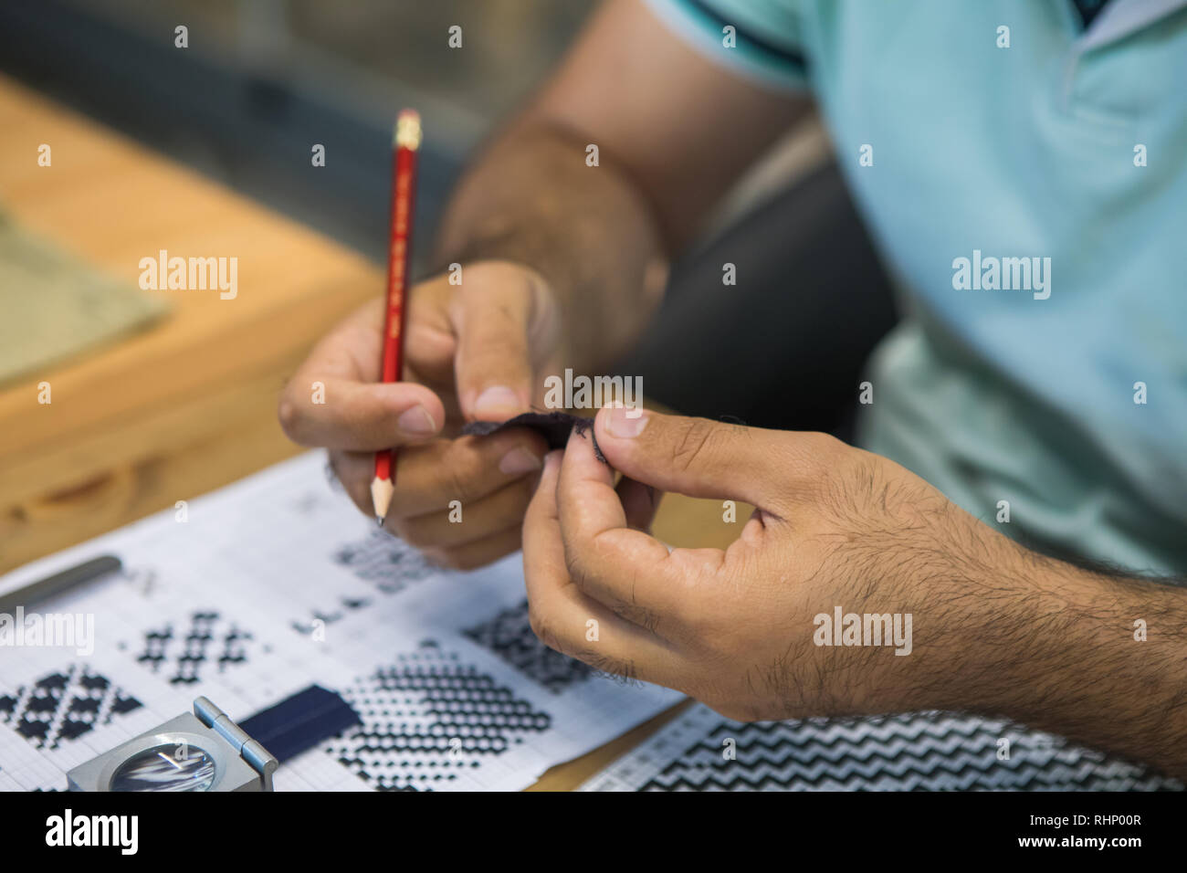 Man holding a piece of fabric and checked tissue for quality control. Textile industry concept background image. - Stock Image