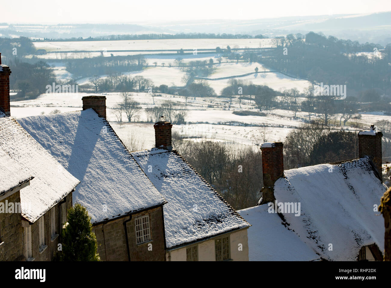 Snowy rooftops and chimneys of cottages  lining the famous Gold Hill against a backdrop of the Blackmore Vale. 2.2.2019. Shaftesbury North Dorset Engl - Stock Image