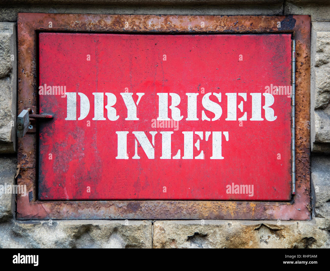 Padlocked entrance to a dry riser inlet with white stencil text against a red background and rusted metal edge on stonework Liverpool January 2019 Stock Photo