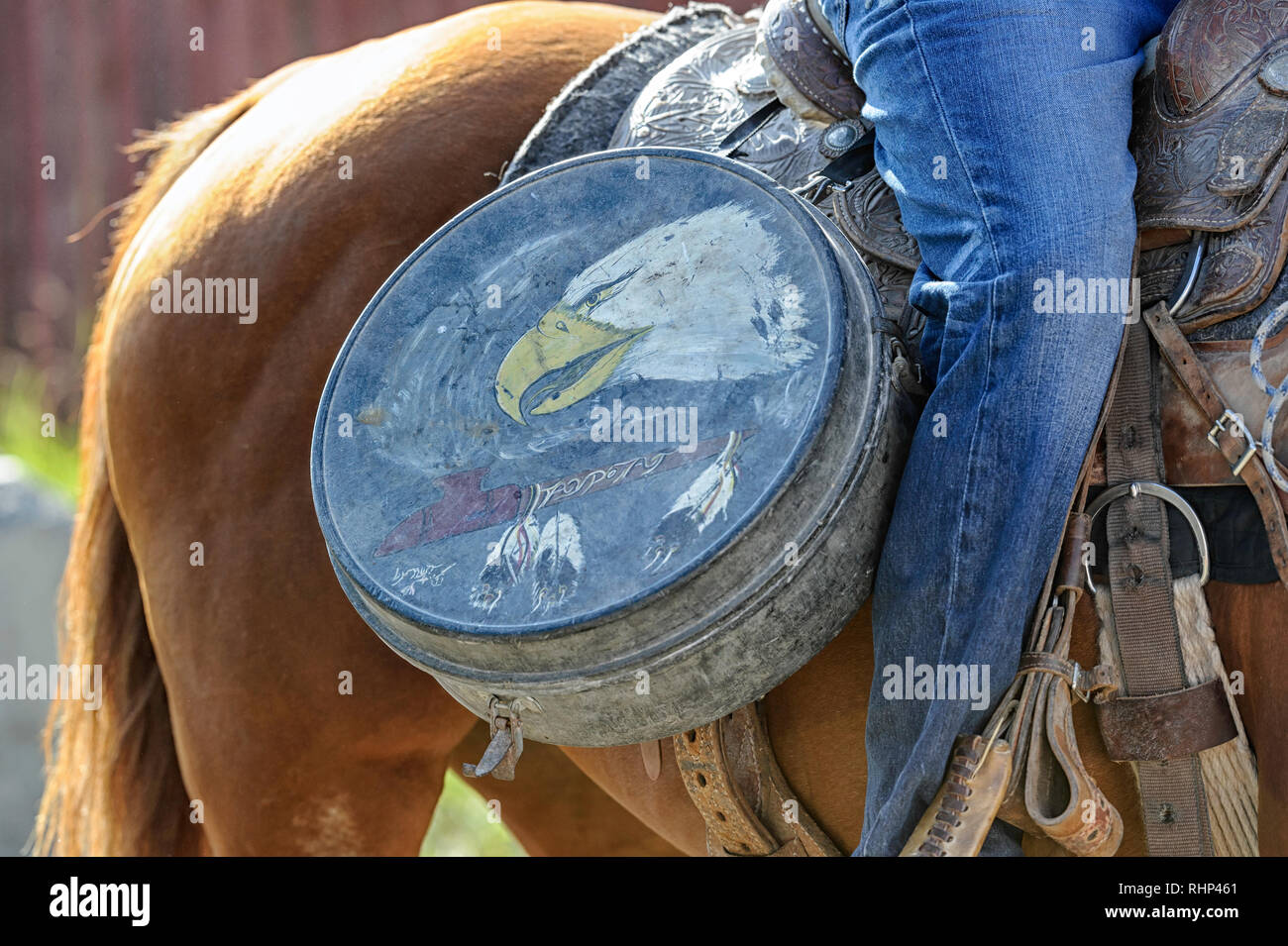 Native cowboy with a vintage western americana lariat lasso galvanized tin carry case in the warm-up arena at the Tsuut'ina Annual Rodeo & Powwow - Stock Image