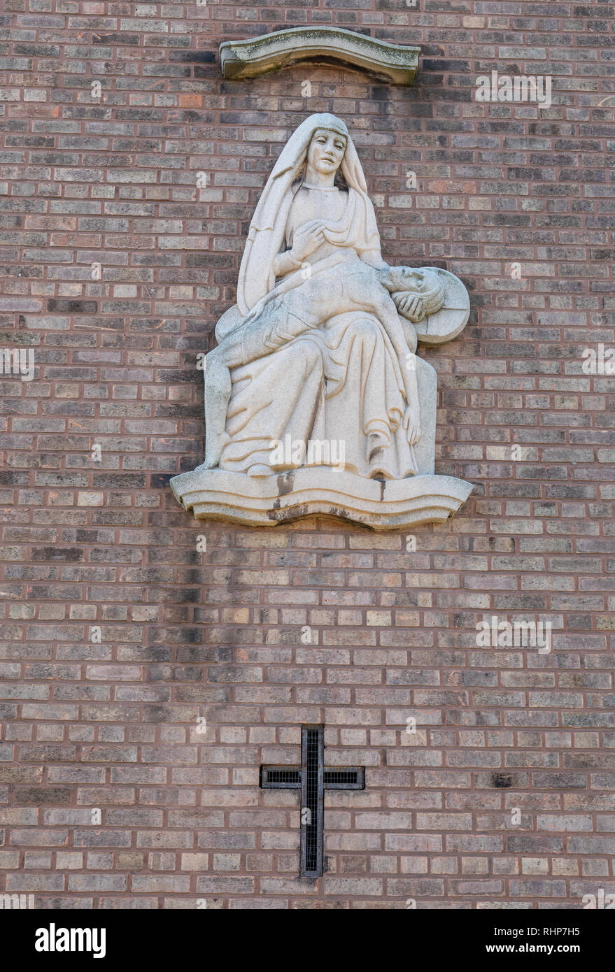 Stone relief of Mary holding the crucified body of Jesus with a cross mounted into the wall of the Holy Apostle and Martyrs Roman Catholic Church Wall Stock Photo