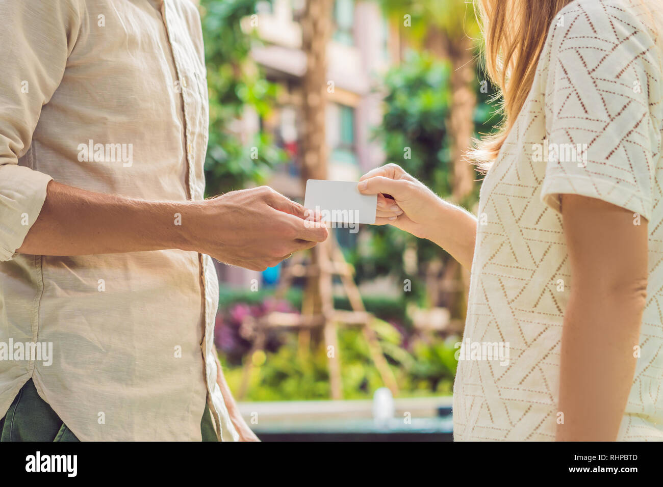 A woman gives to a man security key card or business card - Stock Image