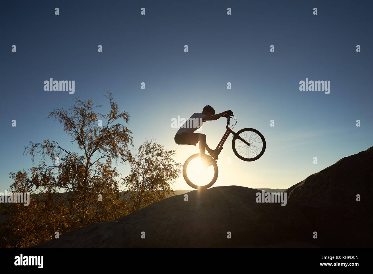 Silhouette of cyclist riding on back wheel on trial bike. Strong sportsman rider balancing on the edge of big rock on the top of mountain at sunset. Concept of extreme sport active lifestyle Stock Photo