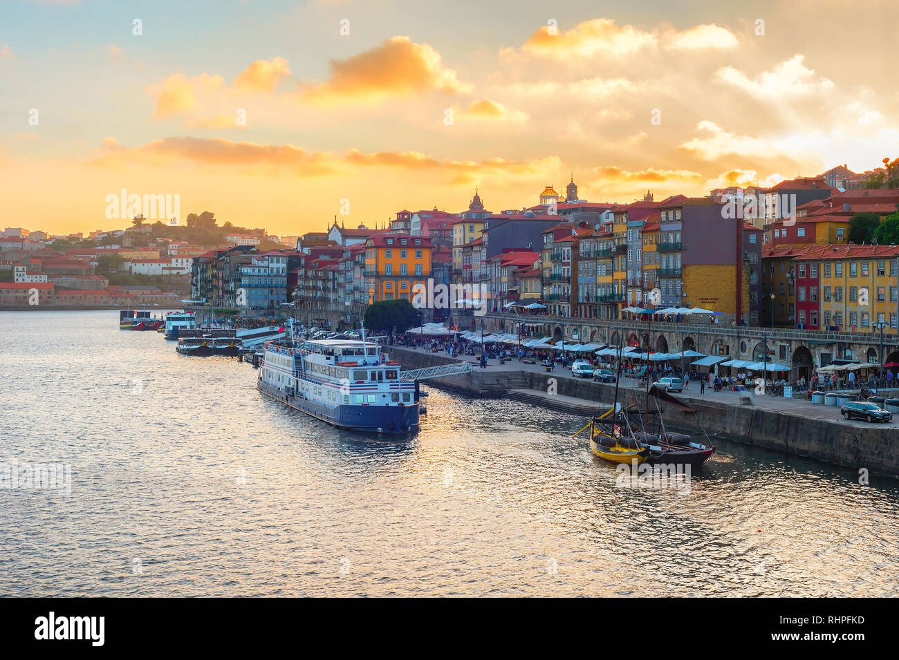 Sunset sky above Porto skyline, embankment with tour boats and wine ships at Douro river, tourists walking and sitting in restaurants of historical do - Stock Image