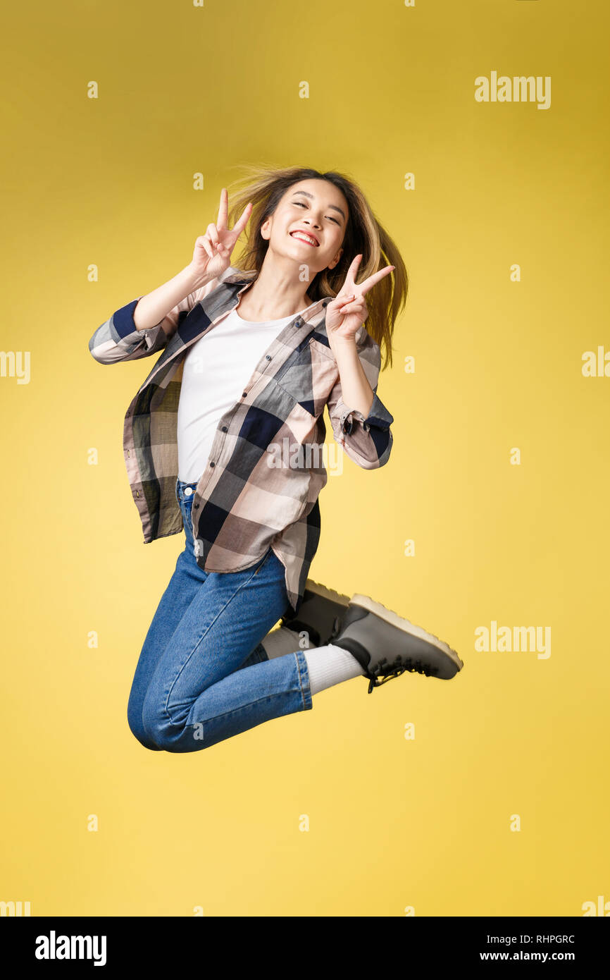 Vertical full length body size studio photo portrait of pretty careless successful glad lady student show her make v-sign near eyes face jumping up. - Stock Image