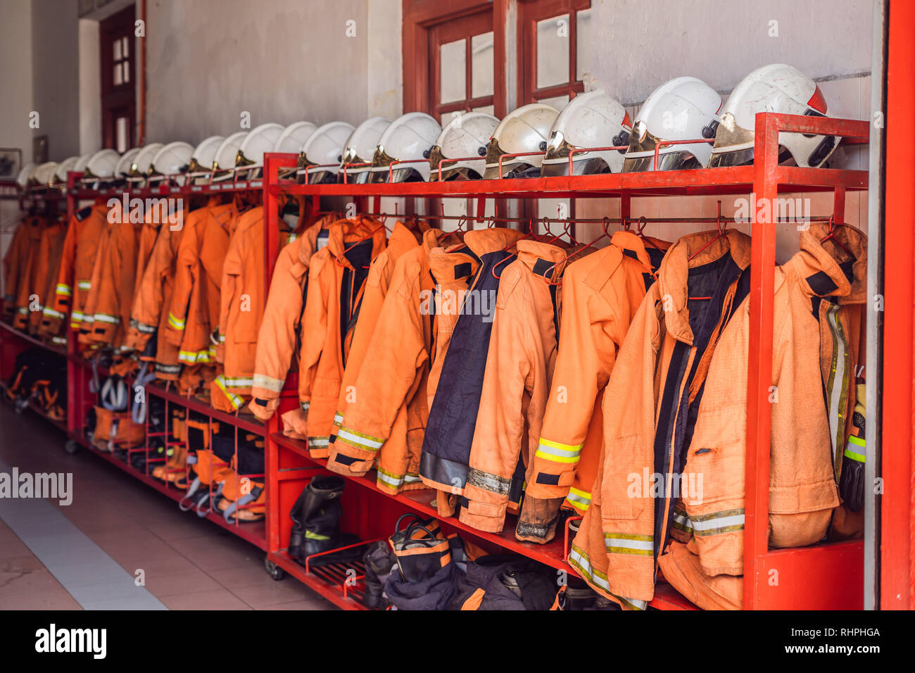 Close up of Fireman coats, helmets and boots wait for the next call. Dressing room of the volunteer fire department - Stock Image