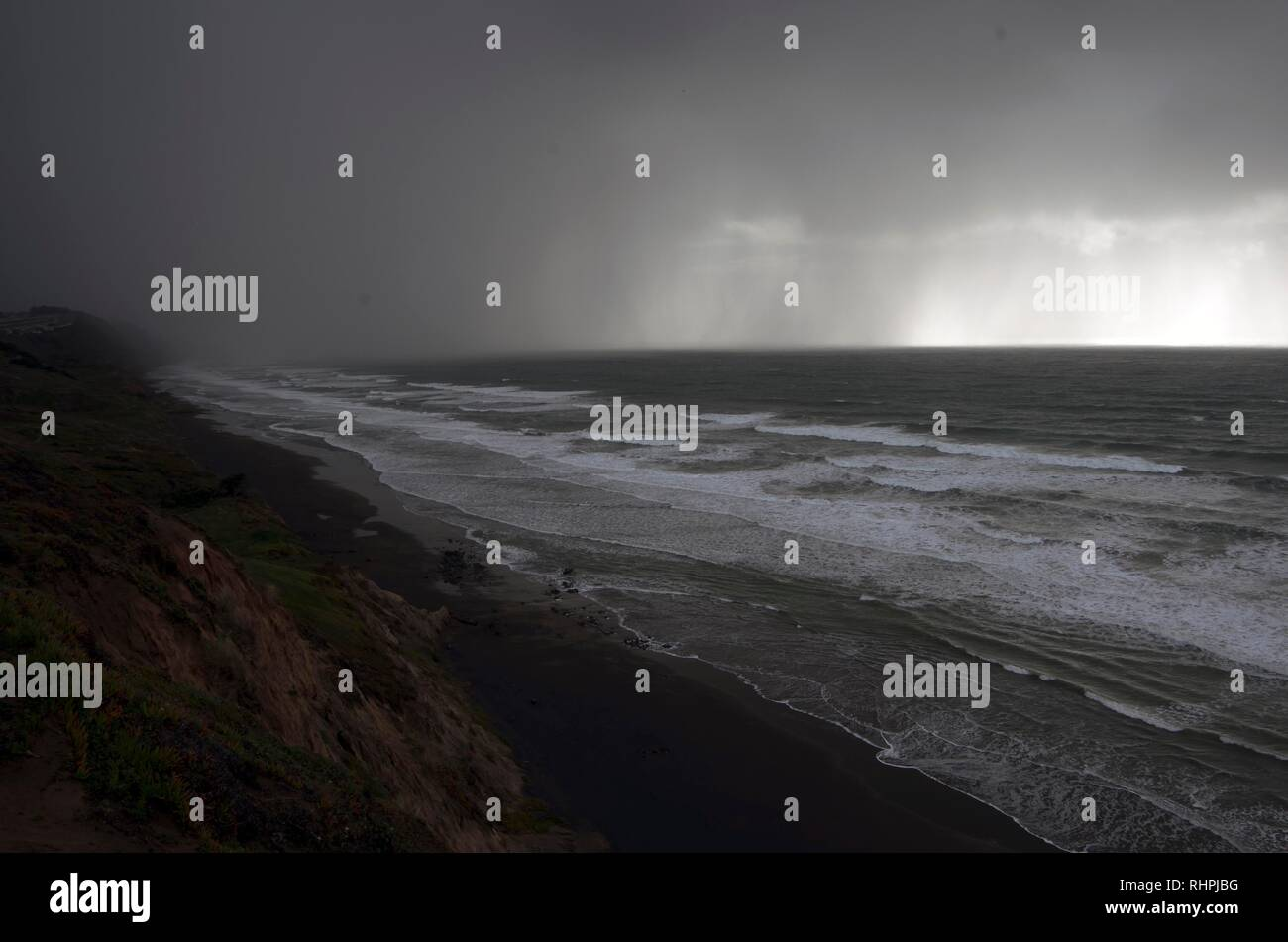 A heavy rain shower approaches Fort Funston near San Francisco. - Stock Image
