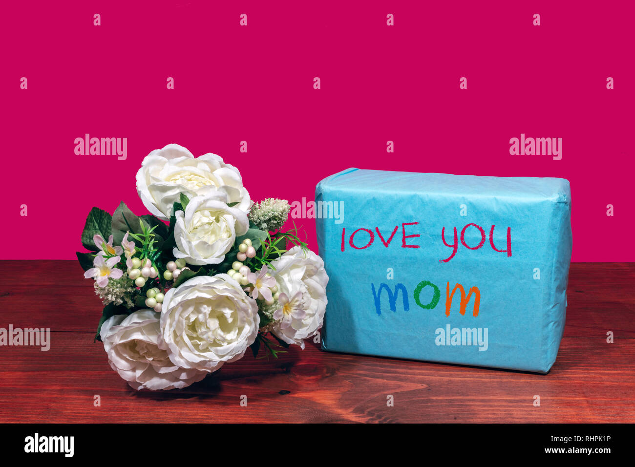 """Beautiful bouquet of arranged flowers and a present with a message """"Love You Mom"""" on a wooden table. mothers day, Easter, valentines, birthday, Christ Stock Photo"""