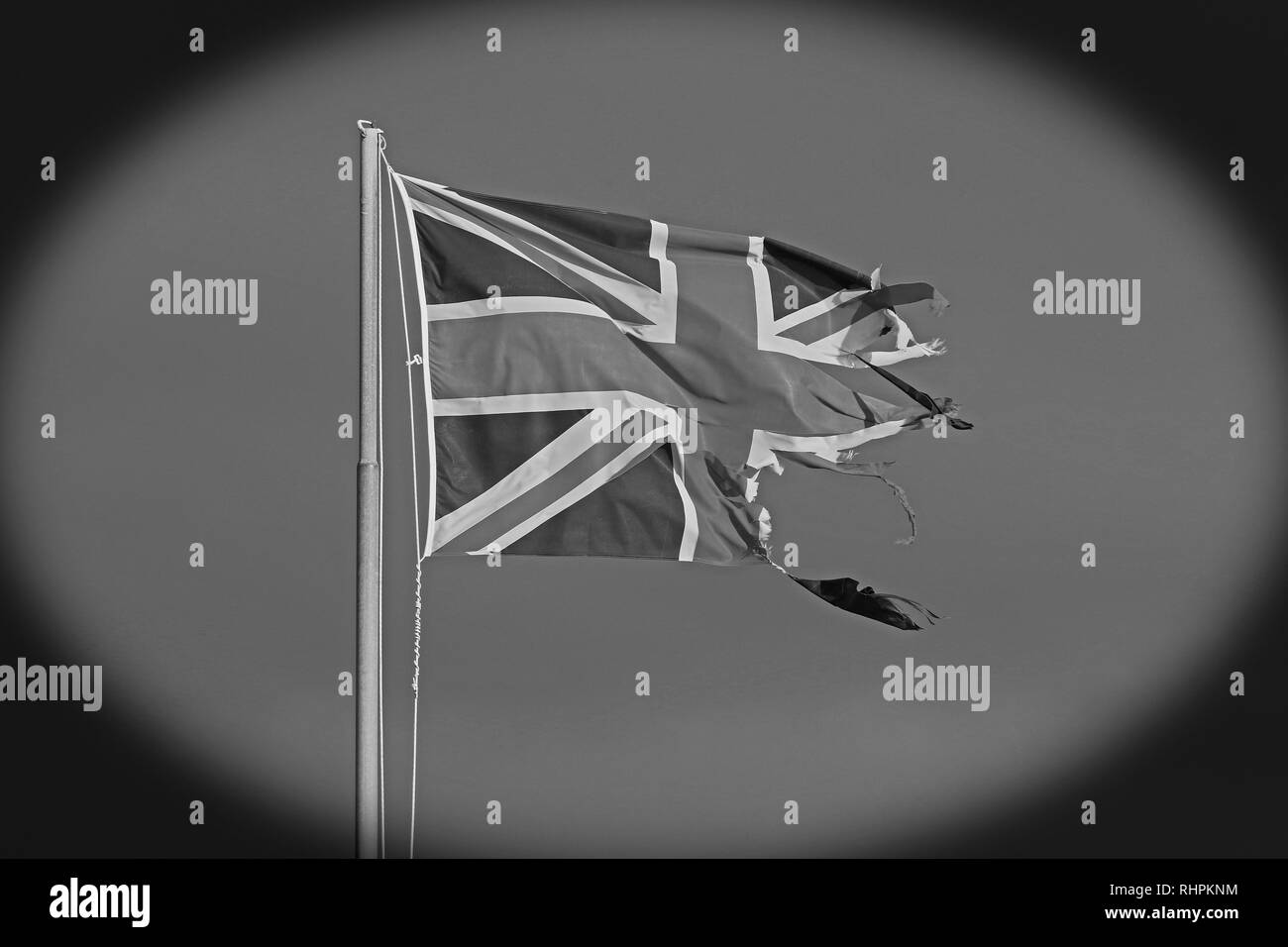 black and white or monochrome image of a British flag or Union Jack torn and tattered flying by the sea in Italy symbol of the Brexit disaster - Stock Image