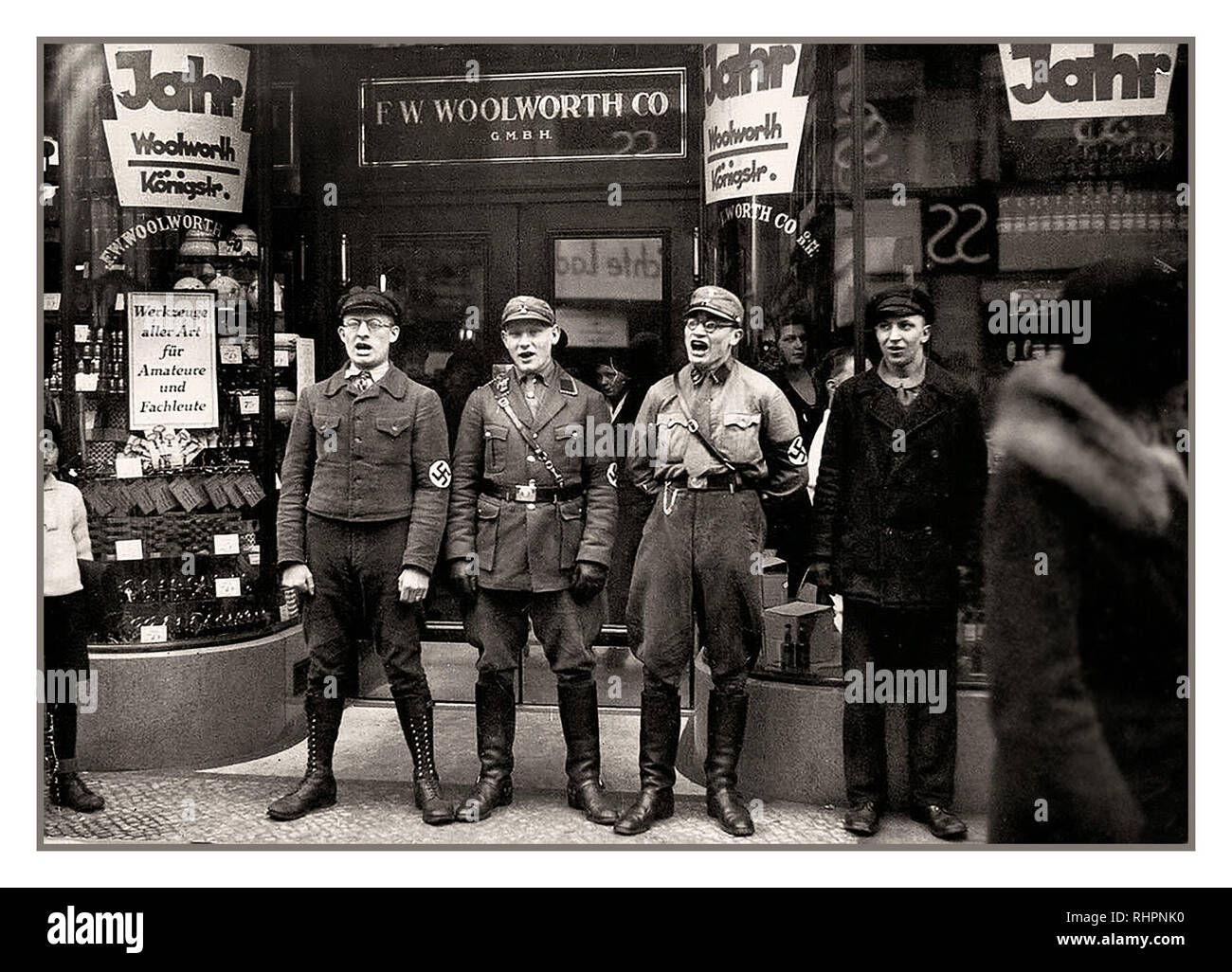 1930's anti-Jewish Nazis and NSDAP party members indulge in racist anti Jewish chanting, at entrance to German high street Woolworth store, to promote a boycott of the allegedly Jewish-founded Woolworths Germany 1933. - Stock Image