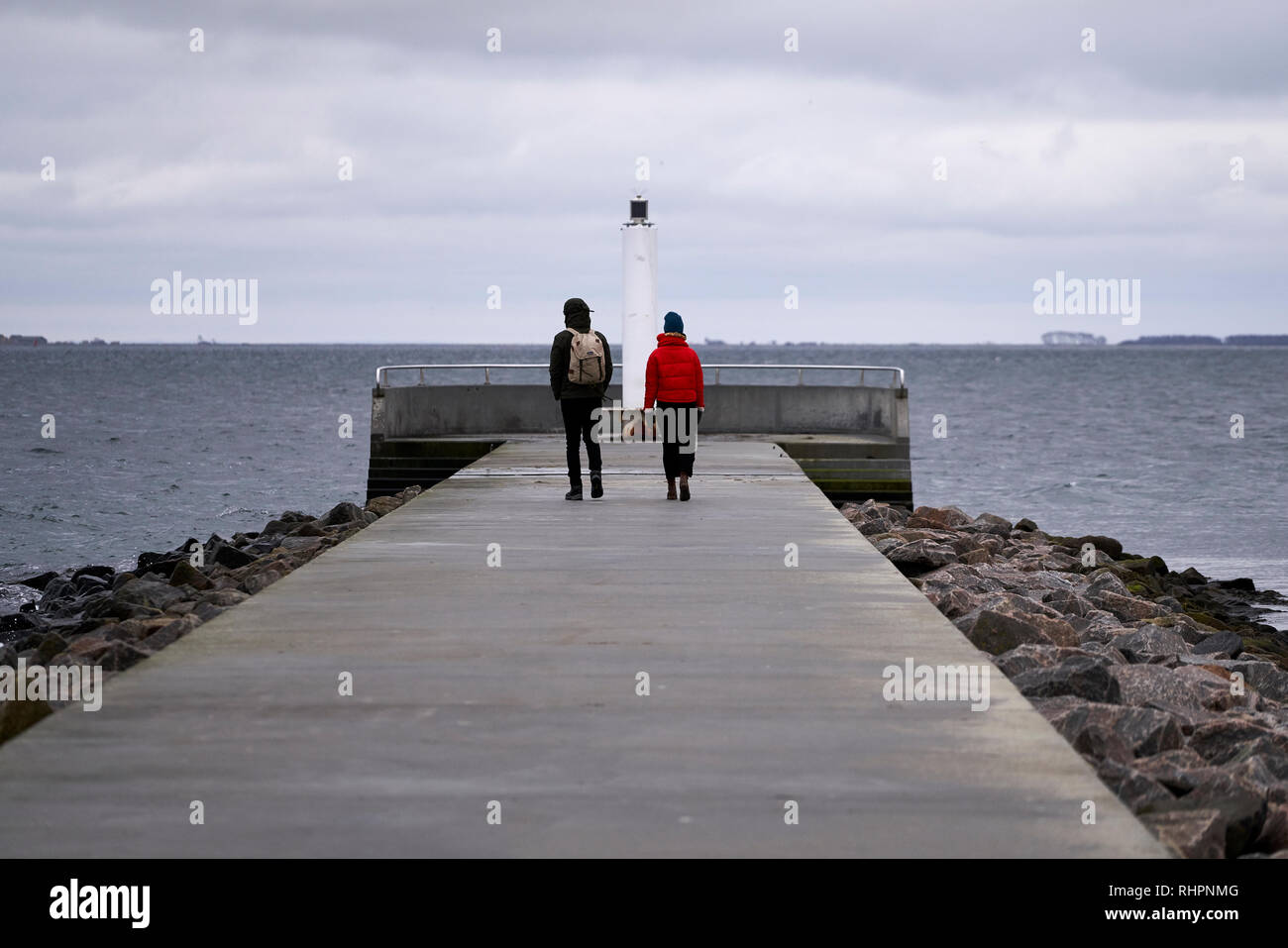 Couple standing on a pier looking out to sea, Copenhagen, Denmark, January 2019 - Stock Image