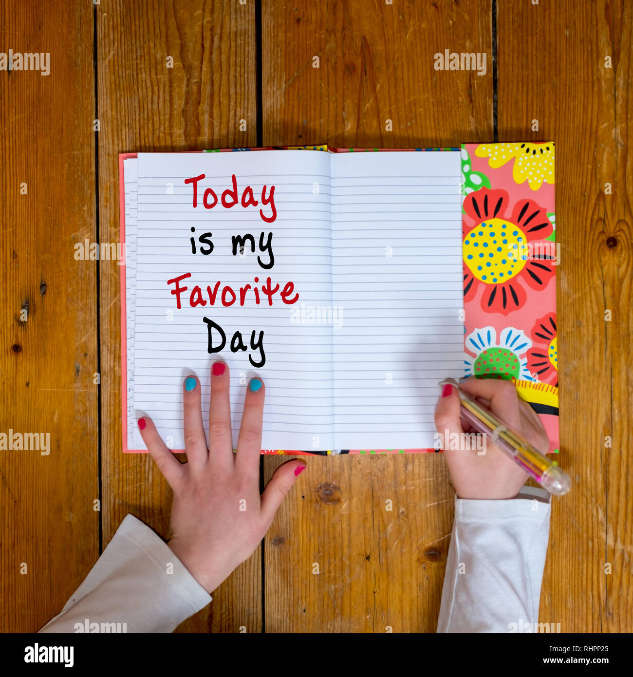 Young girl writing the words Today is my Favorite day in a vintage diary - Stock Image