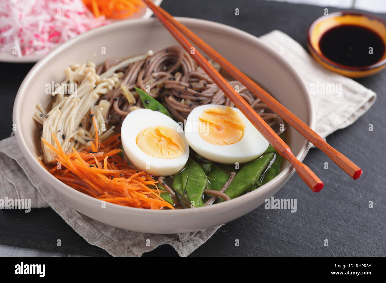 Japanese soup with Enoki mushrooms, soba noodles, boiled egg, carrot, radish, green beans, and soy sauce - Stock Image