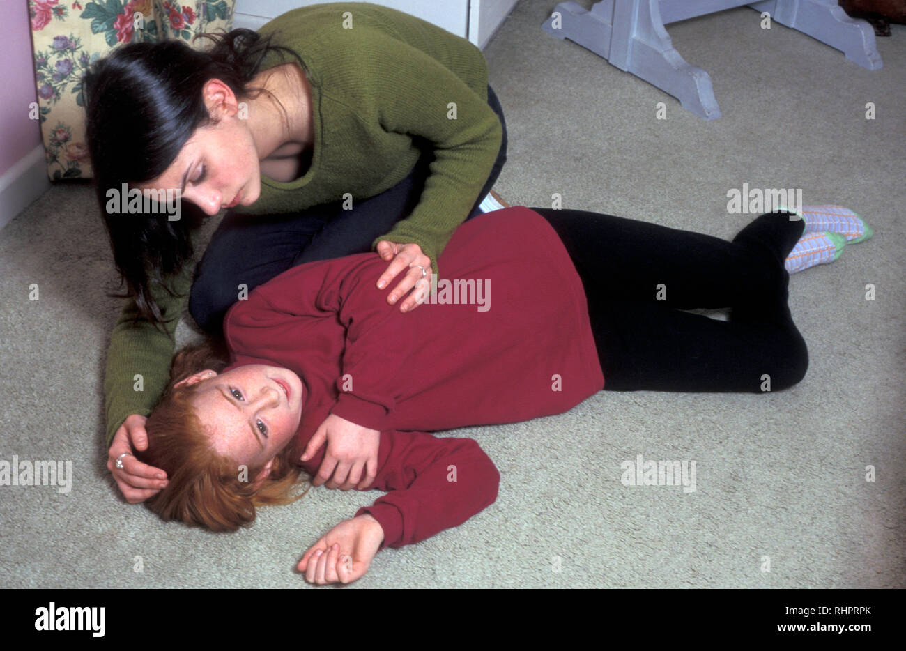 young woman or teenage sibling comforting girl who is lying on floor after shock or epileptic fit - Stock Image