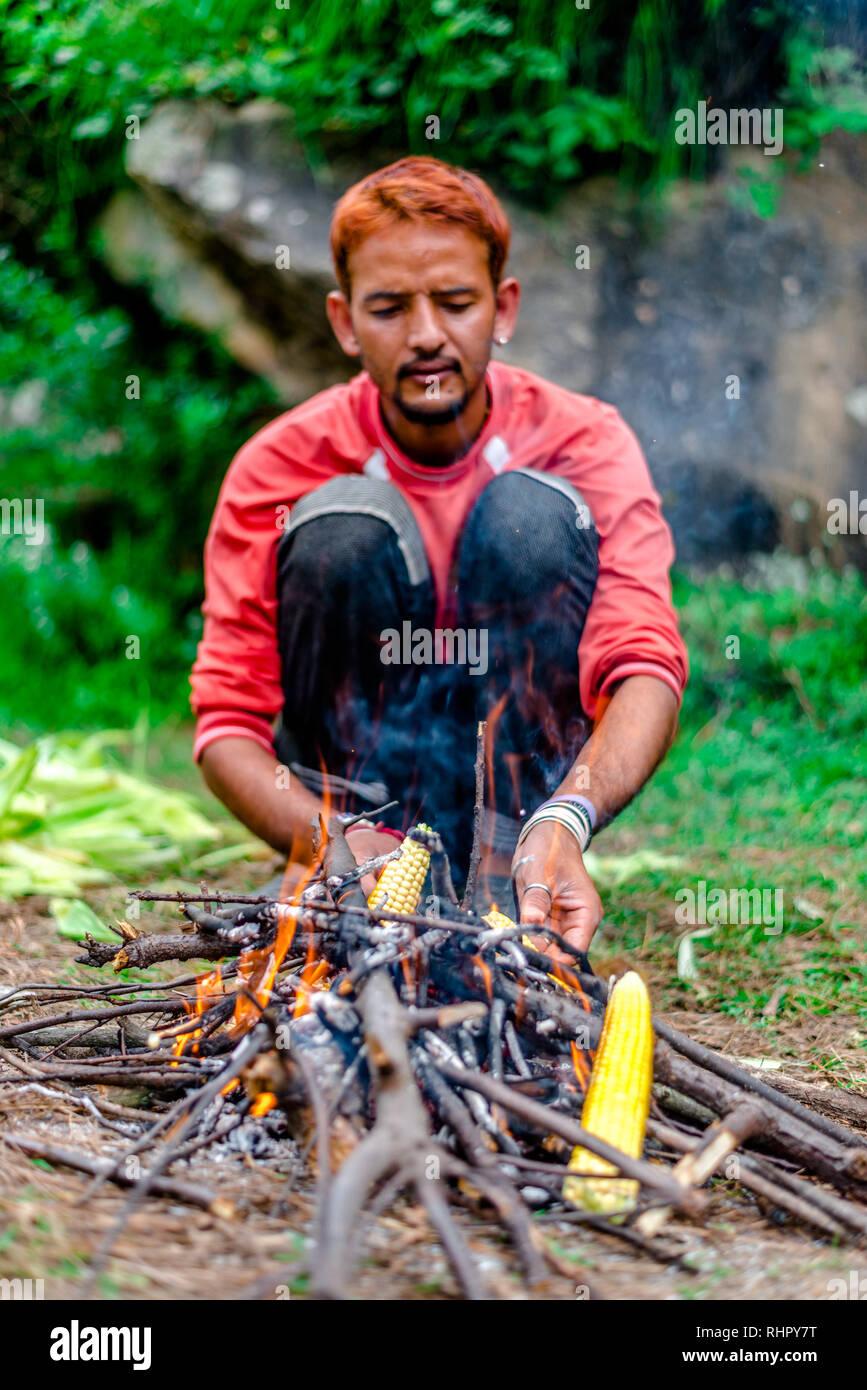 Kullu, Himachal Pradesh, India - September 03, 2018 : Grilling Corn on Bonfire in Himalayas, India - Stock Image