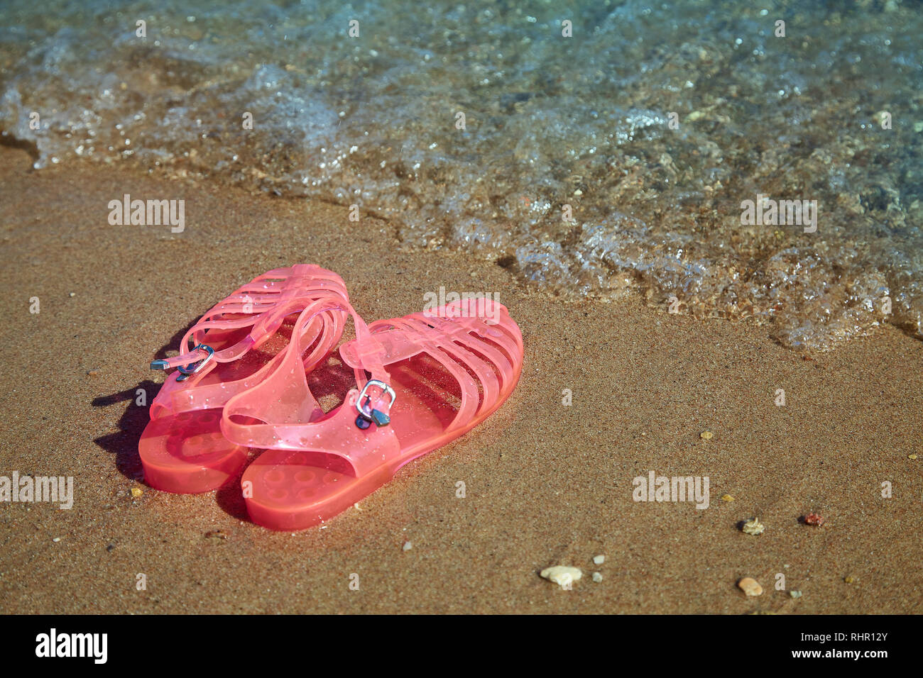 Pink Women's JELLY  SANDALS on a sea shore. LADIES FLAT JELLIES SUMMER BEACH SHOES. Sand background - Stock Image